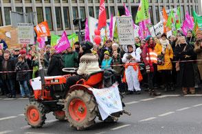 """Eine Frau mit kleinem Traktor fährt an winkenden Demonstranten mit Fahnen vorbei. Demo """"Wir haben es satt"""" in Berlin 2017. Foto: Helga Karl"""