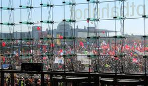 Hinter der Fensterfront des BerlinerHauptbahnhof sind Zehntausende Demonstranten mit Fahnen gegen TTIP und CETA zu sehen. Foto: Helga Karl