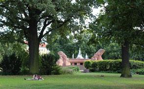 Menschen liegen auf dem Rasen unter Bäumen. Arnswalder Platz mit Stierbrunnen: Foto: Helga Karl