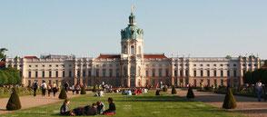 Menschen sitzen auf dem Rasen vor dem Schloss Charlottenburg. Foto: Helga Karl