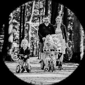 Fotoshooting Oldenburgerland. Familienfotos. Mutter, Vater und Kind auf einem Feld im Stroh. Zusammensein.