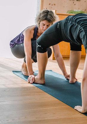 Ich unterstütze Yogaschüler, indem ich sie durch Berührung sanft korrigiere in ihren Yoga-Positionen. Durch Berührung richtet sich die Aufmerksamkeit auf diese Körperregion.