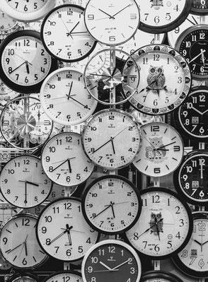 Image en noir et blanc d'horloges différentes.