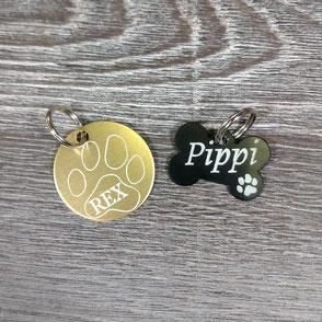 Eine goldene Hundemarke graviert mit Pfote und Rex und eine schwarze Hundemarke in Knochenform graviert mit Pippi.