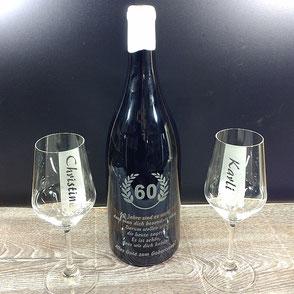 Eine gravierte Weinflasche und zwei gravierte Weißweingläser.