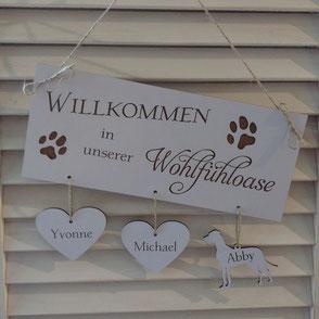 weißes Holzschild mit zwei Herzen und einem Hund graviert mit Namen.
