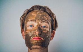 Kille med lermask i ansiktet
