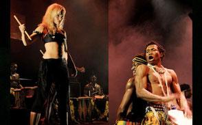 Man spelar trummor och kvinna står bredvid