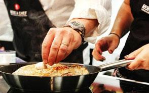 hand som kryddar mat i stekpanna