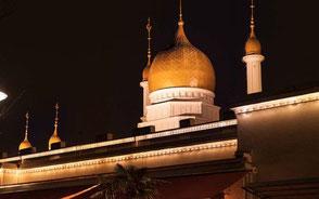 byggnad med upplyst moské i bakgrunden