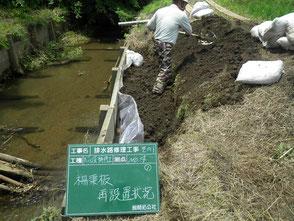 崩壊した排水路のコンクリート製擁壁を修理している写真