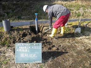 新しく設置した水閘を、手作業で必要な高さまで埋め戻ししている写真。