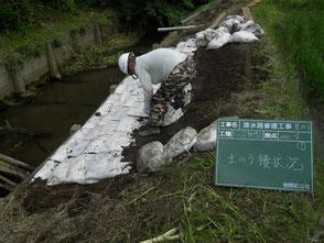 崩落した部分に、盛土をして最後に土嚢を取付作業を完了している写真