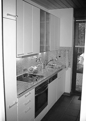 Küche mit Granit-Arbeitsfläche und Küchenspiegel