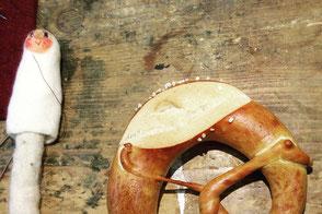 Brezel und halbfertige Fingerpuppe auf einem Tisch im Atelier von Faserverbund