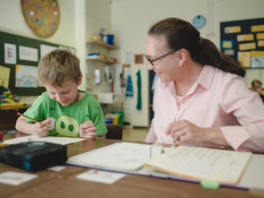 Das Bild zeigt einen Jungen zusammen mit seiner Schulbegleiterin. Foto: Lebenshilfe Soltau e. V.