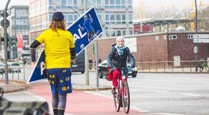 SignSpinner mit begeisterter vorbeifahrender Radfahrerin.