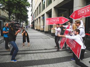SignSpinner posieren für eine Filmaufnahme bei einer Werbekampagne.
