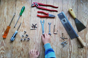 Aufsicht: Kinderhand greift nach sortiertem Werkzeug