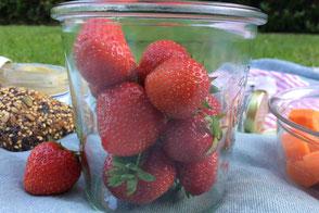 Erdbeeren im Glas auf Picknickdecke