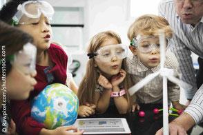 Kinder und Lehrer tragen Schutzbrillen und pusten aufkleines Windradmodell