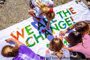 """Jugendliche malen Transpartent, darauf steht """"we are the change"""" Hoffnung für bessere Zukunft und Klimaschutz"""