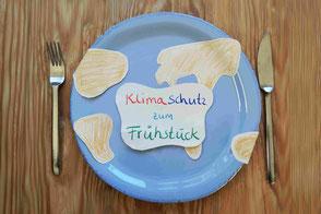 Blauer Teller mit Kontinenten aus Papier, darauf Zettel Klimaschutz zum Frühstück, Besteck neben dem Teller