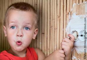 Kleiner Junge schuat in Kamera und zieht Stecker aus Steckdose