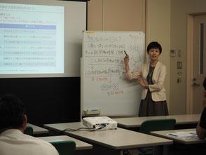 セミナー講師として登壇中の当事務所代表・高島あゆみ。ホワイトボードにいろいろ書き込んで説明しています。