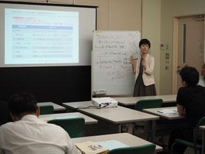 セミナー講師として登壇中の当事務所代表・高島あゆみ。ホワイトボードの前でなにやら力説しています。
