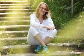 Barbara sitzt in der Natur auf einer Steintreppe und telefoniert.