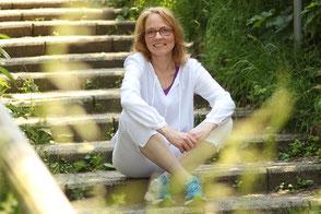 Barbara sitzt entspannt in der Natur auf einer Steintreppe und lächelt.