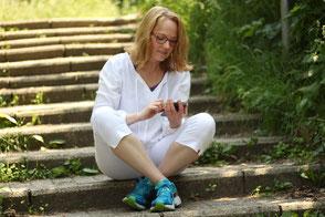 Barbara sitzt in der Natur auf einer Steintreppe und tippt einen Text ins Handy.