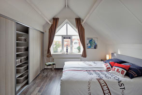 Schlafzimmer mit Boxspring-Doppelbett und geräumigem Einbauschrank