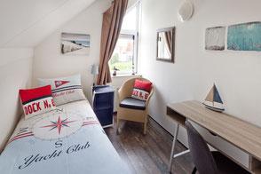 Schlafzimmer mit einem Einzel-Boxspringbett und Schreibtisch