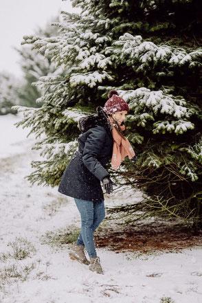 Hübsche Frau steht mit Mütze und Schal im Wald