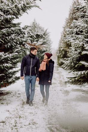 Paar läuft gemeinsam durch schneebedeckten Wald