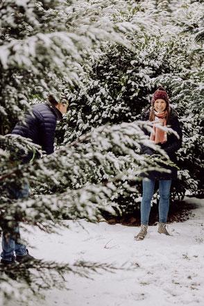Paar steht lachend zwischen schneebedeckten Tannen
