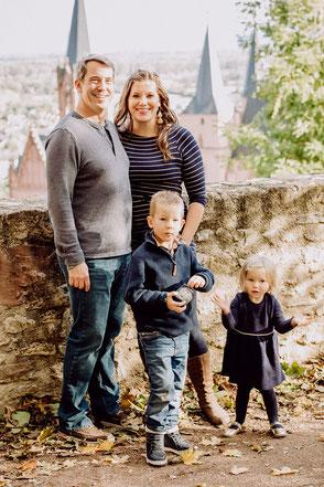 Eltern und Kinder stehen vor einer Mauer