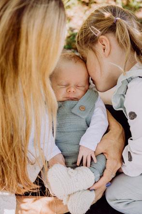 Familie kuschelt mit Baby bei Fotoshooting