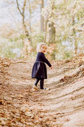 Mädchen in blauem Kleid steht im Wald