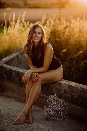 Portrait einer jungen Frau, die im Sonnenuntergang bei Mainz auf einer Mauer sitzt