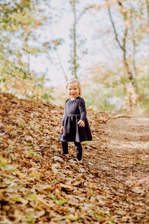 Kleines Mädchen im Kleid lächelt in die Kamera