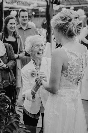 Grossmutter gratuliert lächelnd der Braut bei Hochzeitsfeier in Ladenburg