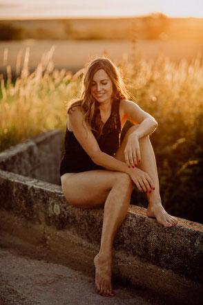 Auf einer Mauer sitzt eine junge Frau lässig im Sonnenuntergang