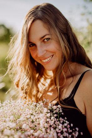 Portrait einer lächelnden Frau bei untergehender Sonne