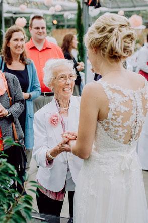 Grossmutter hält die Hände der Braut