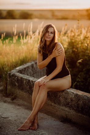 junge Frau sitzt auf einer Mauer im Sonnenuntergang