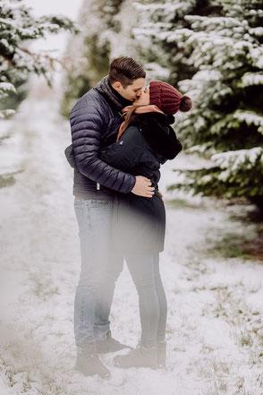 Pärchen steht küssend im Schnee im Wald