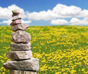 Zu sehen ist eine grüne Wiese mit vielen gelben Butterblumen, blauer Himmel mit Wolken und ein Steintürmchen links vorne im Bild. Ein Bild, das für achtsame Kommunikation steht – erlernbar im MBSR-Kurs Frankfurt von Heike Merkle.